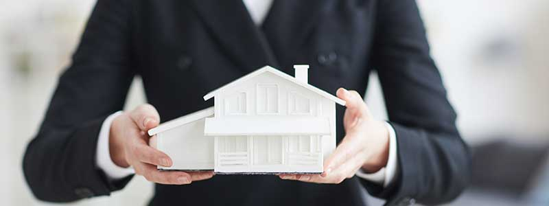 Mortgage information woman holds model of house
